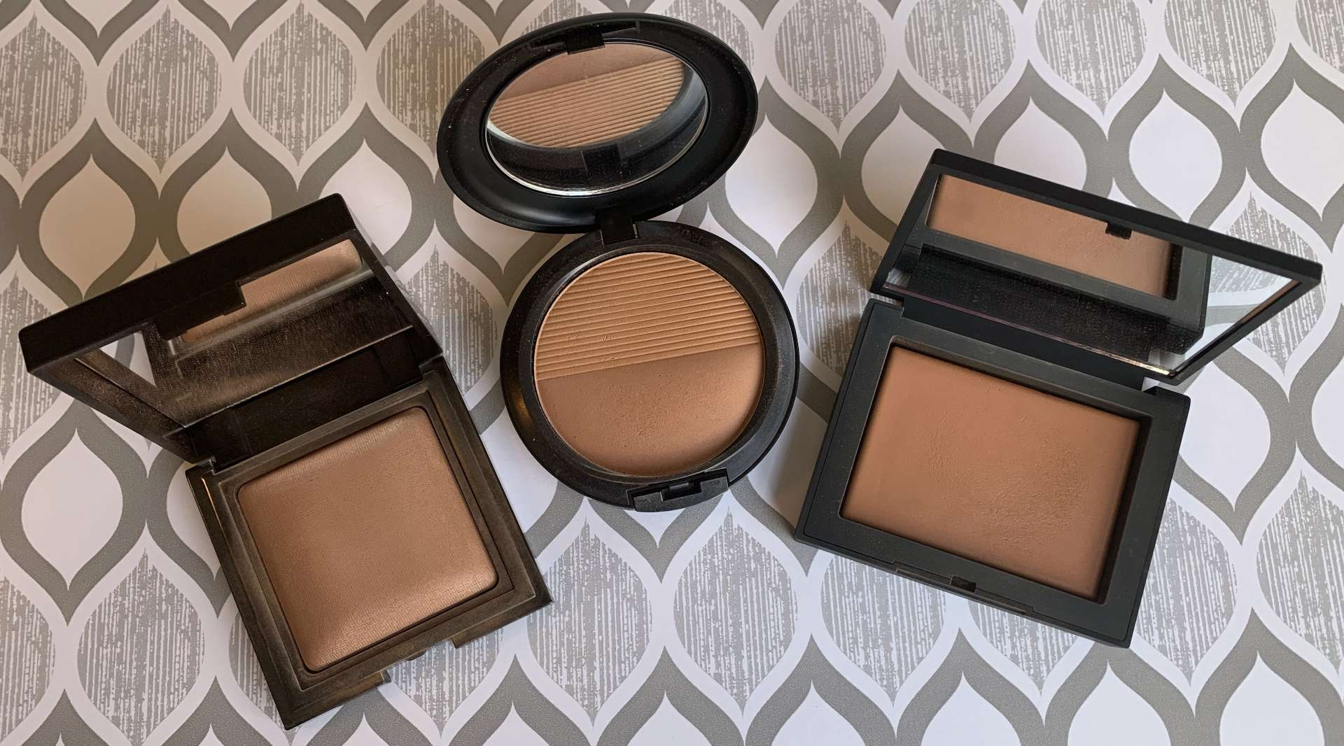 Laura Mercier Candleglow Sheer Perfecting Powder (5), MAC Studio Waterweight Pressed Powder (dark), and NARS Light Reflecting Pressed Setting Powder (sunstone)